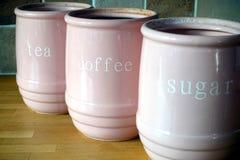 Drie roze kruiken op een houten oppervlakte van het keukenwerk, met de woorden Stock Fotografie