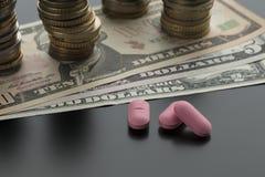Drie roze pillen, tabletten met dollarrekeningen en stapels muntstukken royalty-vrije stock afbeeldingen