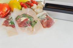 Drie ruwe lapjes vlees in vacuümverpakking en vacuümverpakker Sous -sous-vide, nieuwe technologiekeuken stock foto's