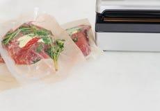 Drie ruwe lapjes vlees in vacuümverpakking en vacuümverpakker Sous -sous-vide, nieuwe technologiekeuken royalty-vrije stock foto