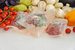 Drie ruwe lapjes vlees in vacuümverpakking, groenten en paddestoel Sous -sous-vide, nieuwe technologiekeuken royalty-vrije stock afbeelding