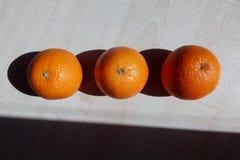 Drie sappige sinaasappelen liggen op een houten lijst stock afbeeldingen