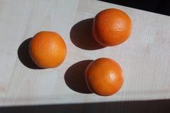 Drie sappige sinaasappelen liggen op een houten lijst stock fotografie