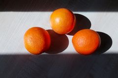Drie sappige sinaasappelen liggen op een houten lijst royalty-vrije stock afbeelding