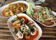 Drie schotels van Thaise zeevruchtenkeuken op de achtergrond van de bamboelijst stock fotografie