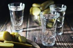 Drie schoten met wodka en ingelegde komkommers stock foto's