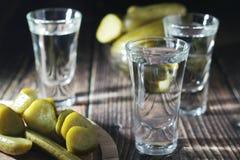 Drie schoten met wodka en ingelegde komkommers stock foto
