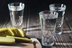 Drie schoten met wodka en ingelegde komkommers royalty-vrije stock afbeeldingen