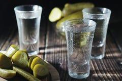 Drie schoten met wodka en ingelegde komkommers stock afbeelding