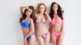 Drie sexy jonge vrouwen die in bikinis dragen