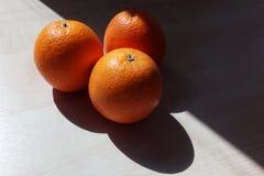 Drie sinaasappelen liggen op een houten lijst in de vorm van een driehoek royalty-vrije stock foto's