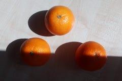 Drie sinaasappelen liggen op een houten lijst in de vorm van een driehoek stock fotografie