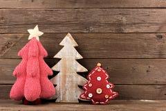 Drie sjofele elegante Kerstbomen tegen hout Stock Foto's