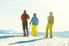 Drie skiërs die klaar voor berijden bergaf vanaf de bovenkant van een berg worden Stock Foto