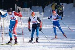Drie skiërs in heldere kleren die zich op een helling bevinden - Rusland Berezniki 11 Maart, 2018 stock fotografie