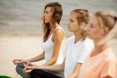 Drie slanke jonge meisjes zitten in de lotusbloemposities met het sluiten van ogen die yoga op matten op zandig strand op een war royalty-vrije stock fotografie