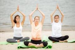Drie slanke jonge meisjes zitten in een yoga stelt met het sluiten van ogen op matten op zandig strand op een warme dag royalty-vrije stock afbeeldingen