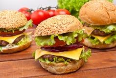 Drie smakelijke cheeseburgers stock fotografie