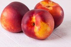 Drie smakelijke verse rijpe sappige nectarines Stock Afbeeldingen