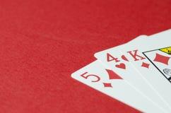 Drie speelkaarten, koning, vijf, vier op rode achtergrond, lege ruimte voor tekst stock afbeeldingen