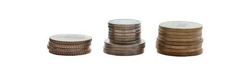 Drie stapels muntstukken op een witte achtergrond Geïsoleerde stock foto's