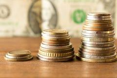 Drie stapels verschillende muntstukken op de achtergrond van 1 dollarbi stock afbeelding
