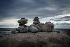 Drie steen` s piramides op de oceaankosten met donkere bewolkte hemelachtergrond stock afbeelding