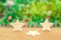Drie sterren, een ster vielen Het concept een daling van classificatie en kwaliteit Ontbering van de derde ster Terugkoppeling ov stock foto's