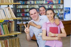 Drie studenten in bibliotheek stock foto