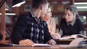 Drie studenten die in bibliotheek zitten en hun onderzoek bespreken stock videobeelden