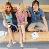 Drie studenten die camera hoogste mening kijken Stock Fotografie