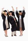 Drie studenten die in gediplomeerde robe hun wapens opheffen Stock Fotografie