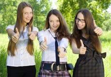 Drie studentenmeisje met duim-omhoog in het park Royalty-vrije Stock Foto