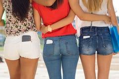 Drie studentenmeisjes met mobiel in de zak Stock Afbeelding