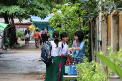 Drie studentes in Myanmarese eenvormig van school wit overhemd en groene Lange Yi bespreken het onderwerp van thuiswerk Stock Foto's