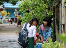 Drie studentes in Myanmarese eenvormig van school wit overhemd en groene Lange Yi bespreken het onderwerp van thuiswerk royalty-vrije stock fotografie