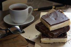 Drie stukken van zandkoek met boeken en koffie Stock Foto