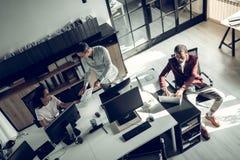 Drie succesvolle zakenlieden die aan project samenwerken stock fotografie