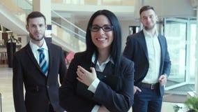 Drie succesvolle zakenlieden kijken in de camera stock video