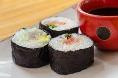 Drie sushibroodjes met een kleine kom van zeggen saus Royalty-vrije Stock Fotografie