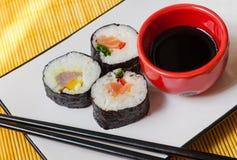 Drie sushibroodjes met eetstokjes en een kom sojasaus Stock Afbeeldingen