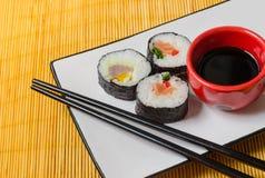 Drie sushibroodjes met sojasaus en eetstokjes Stock Afbeelding