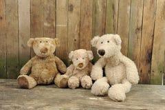 Drie teddyberen gezet tegen een houten muur Stock Foto's