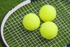 Drie tennisballen liggen op de koorden van een tennisracket. over groen La Royalty-vrije Stock Afbeeldingen