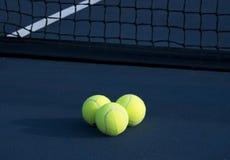 Drie Tennisballen op een Tennisbaan stock afbeeldingen