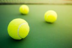 Drie tennisballen op groen hard hof stock foto's