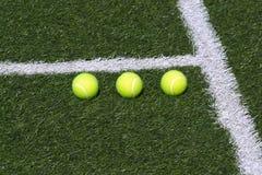 Drie tennisballen op groen hof Stock Afbeelding