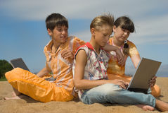 Drie tienerjaren met laptops Royalty-vrije Stock Foto's