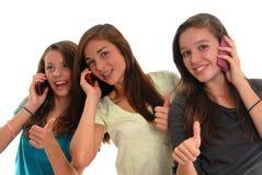 Drie tieners die samen celtelefoons glimlachen Royalty-vrije Stock Afbeelding