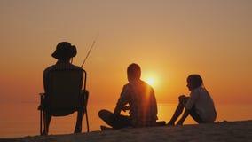 Drie tieners vissen op de kust van het meer bij zonsondergang Gelukkig kinderjarenconcept stock foto